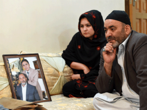 This file photograph shows Syed Qurban (R) sitting with his daughter Fauzia as he speaks during an interview at his residence in Quetta, next to a portrait of his son Ali Raza who was drowned after boarding a ship going illegally to Australia. — AFP